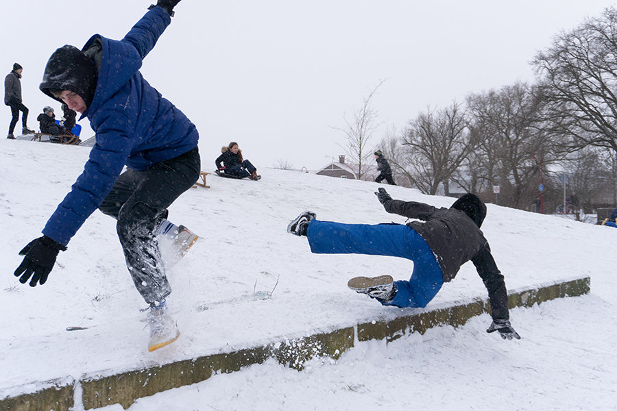 Skateboarders having fun in the winter snow