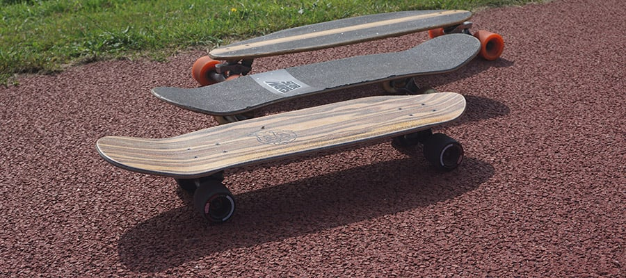 Three different cruiser skateboard setups next to eachother