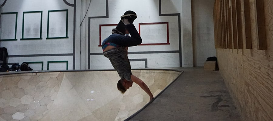 skateboarder performing a handplant in a pool