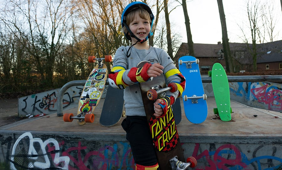 7 year old kid holding a skateboard