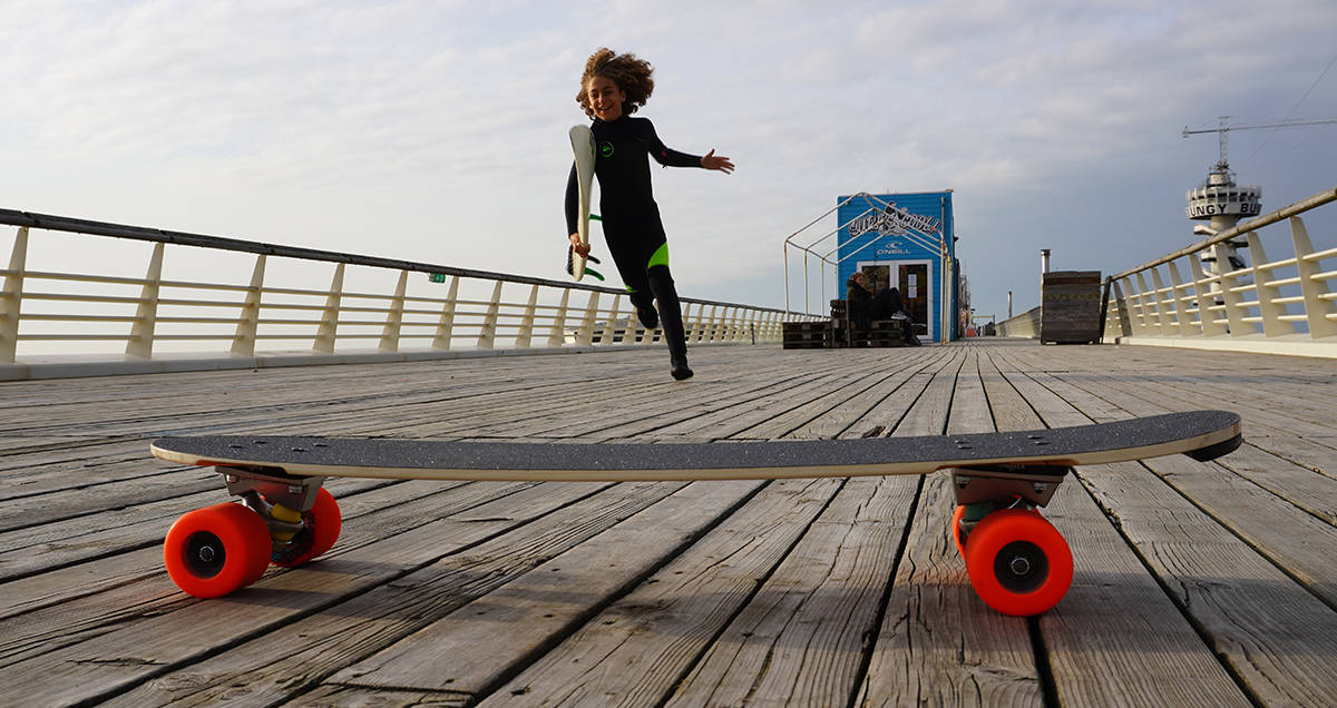 surfer kid and a skateboard on a pier