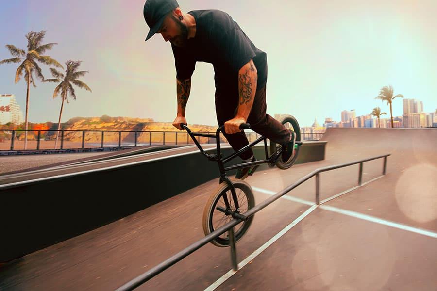 BMX rider is performing tricks in a skatepark