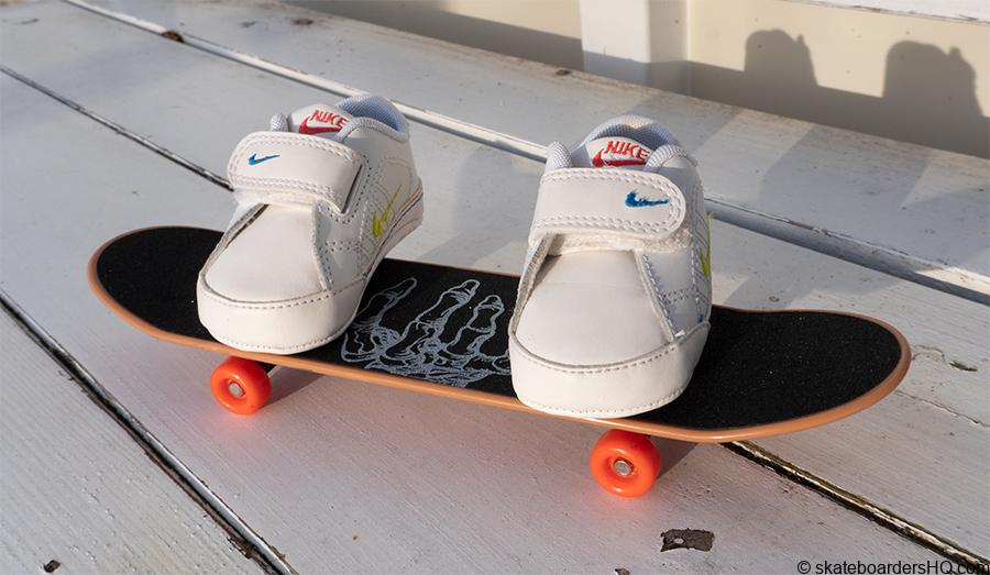 baby sneakers on a hand skateboard