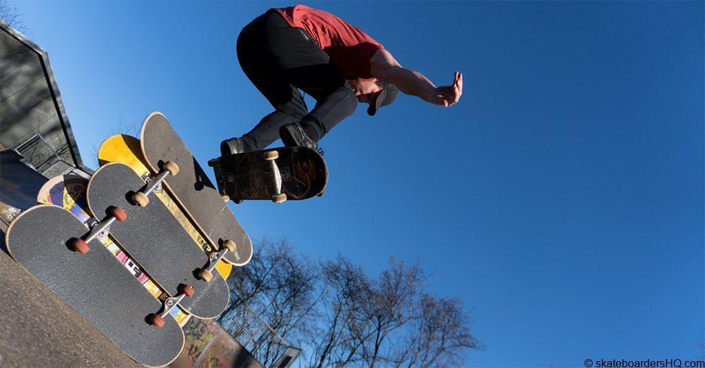 skateboarder ollies over 5 decks